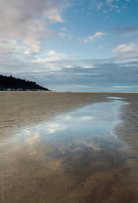 Sunset sky reflected in a water at low tide. Wells-next-the-sea, Norfolk, UK. by Liam Grant for Stocksy United