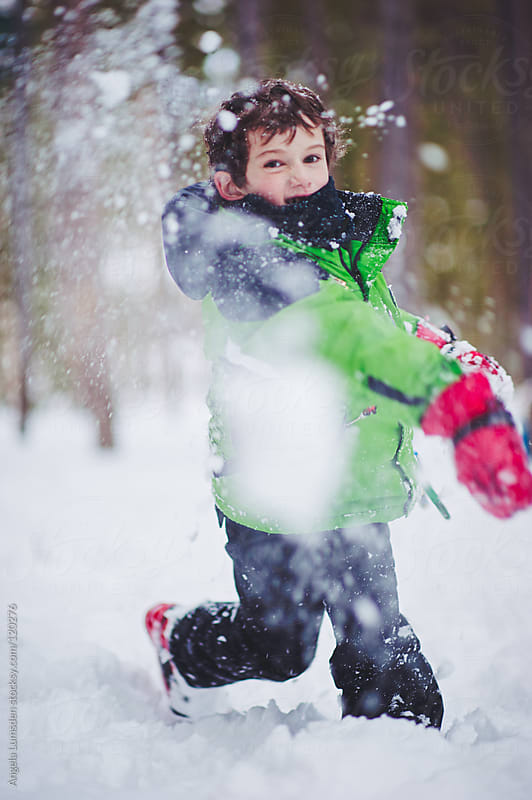 Boy throwing a snowball directly at camera by Angela Lumsden for Stocksy United