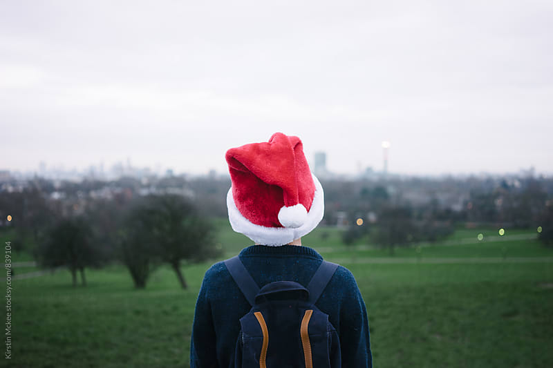 Boy wearing Santa hat, looking out over London by Kirstin Mckee for Stocksy United