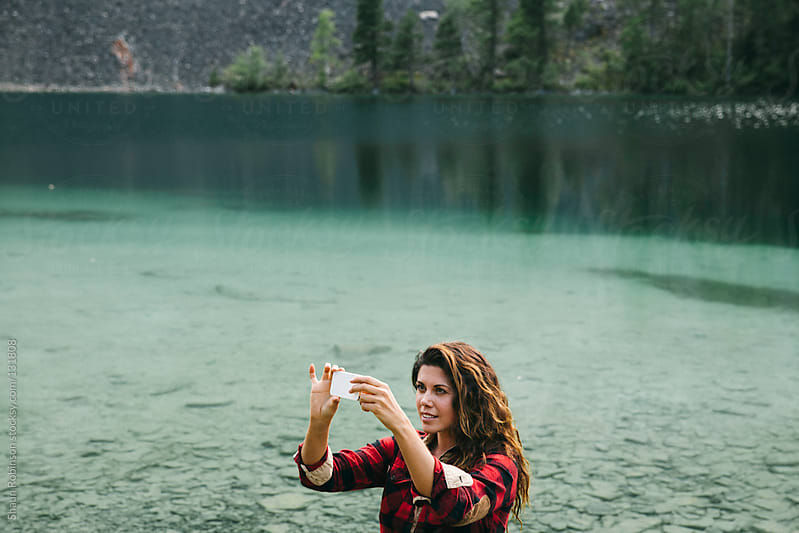 woman taking a picture on a lake by Shaun Robinson for Stocksy United
