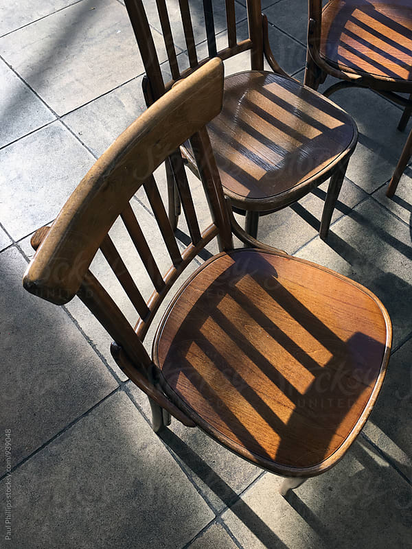 Set of three chairs in sunlight  by Paul Phillips for Stocksy United