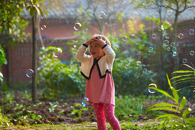 lovely little asian girl playing with bubble outdoor by Bo Bo for Stocksy United