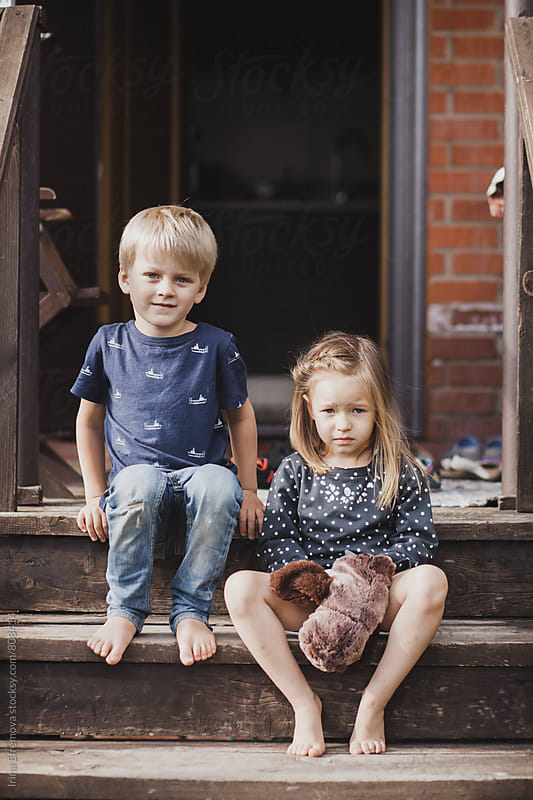 Boy and a girl sitting on a porch by Irina Efremova for Stocksy United