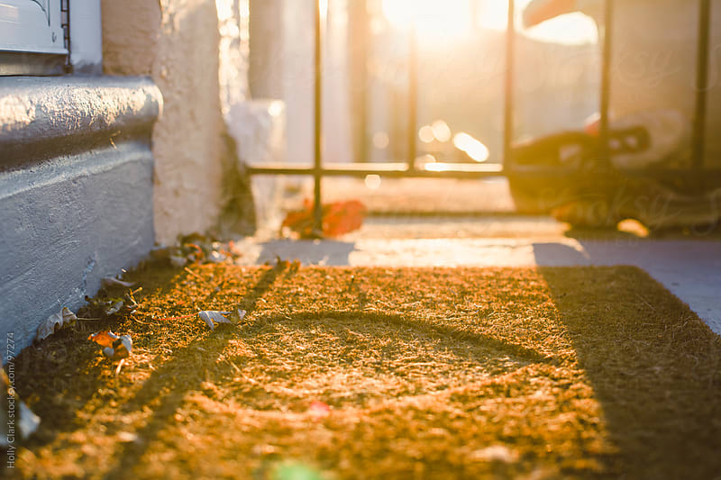 A doormat on a front stoop with autumn leaves. by Holly Clark for Stocksy United