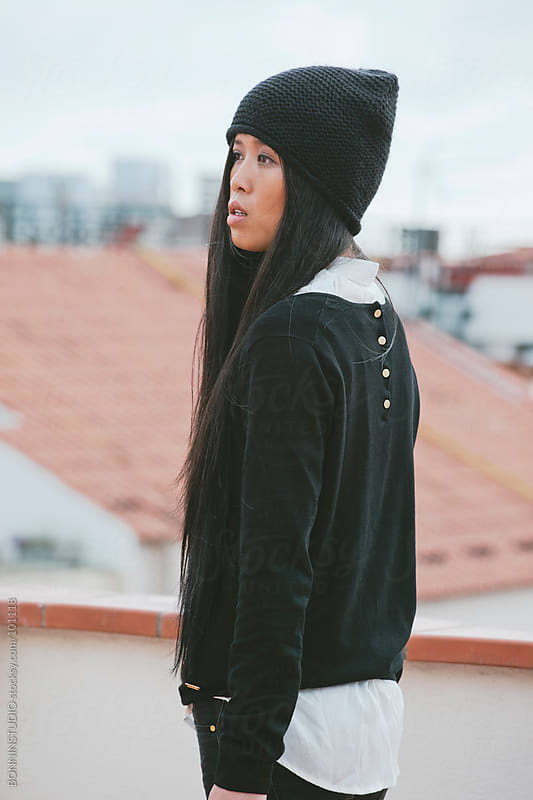 Young chinese woman standing on a terrace overlooking the city. by BONNINSTUDIO for Stocksy United