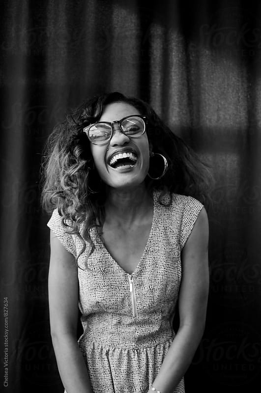 Black and white portrait of a young woman laughing by Chelsea Victoria for Stocksy United