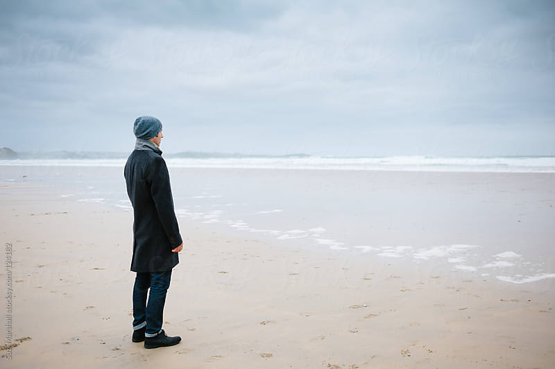 Man standing alone on the beach looking out to sea by Suzi Marshall for Stocksy United