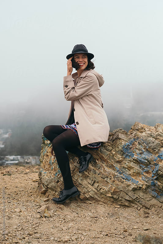 Smiling brunette traveler sitting on rock at viewpoint by Lucas Saugen for Stocksy United