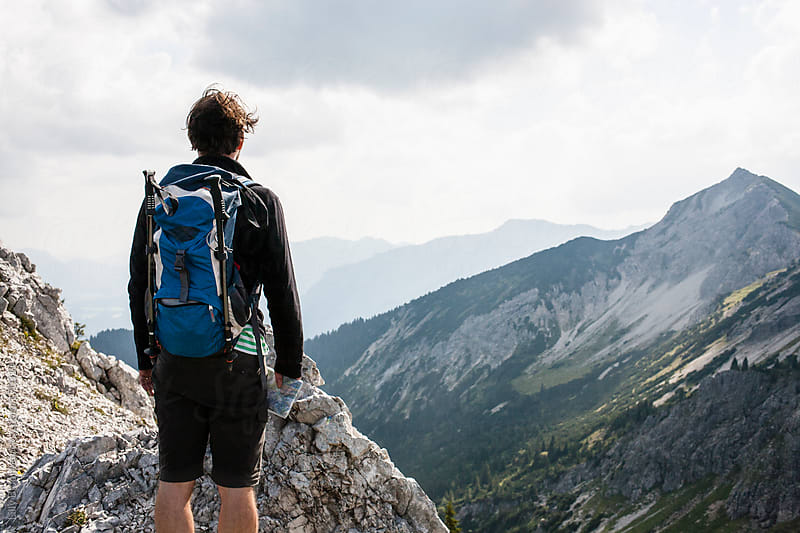 Hiking man enjoying the view of the mountain scenery by Lilly Bloom for Stocksy United