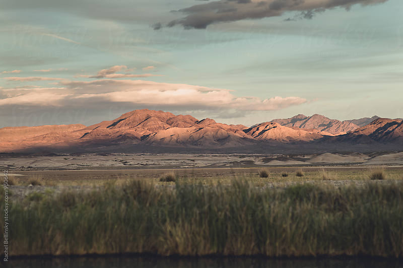 A desert landscape with mountains reflecting pink sunset light by Rachel Bellinsky for Stocksy United