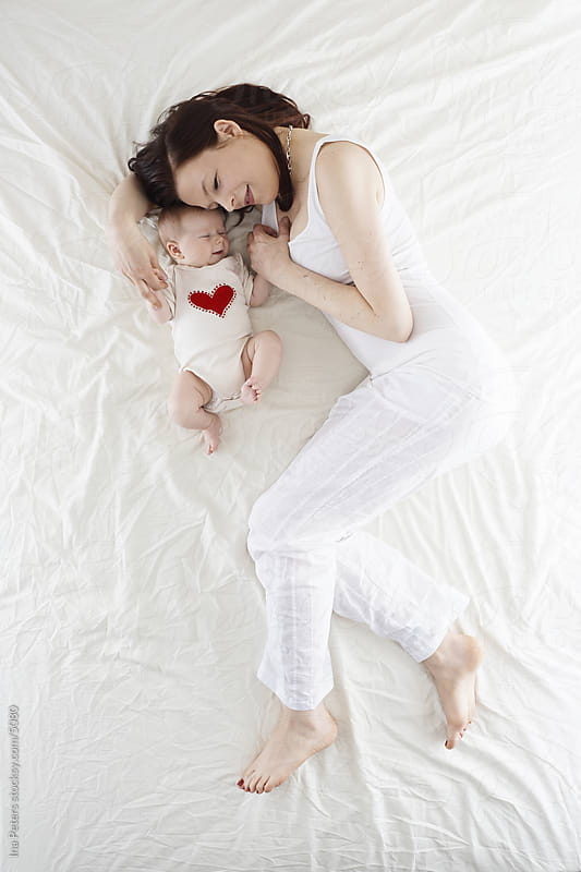 Mother lying in bed with her baby by Ina Peters for Stocksy United