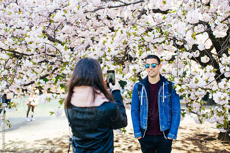 Woman taking a portrait of his friend in front of a cherry tree. by BONNINSTUDIO for Stocksy United