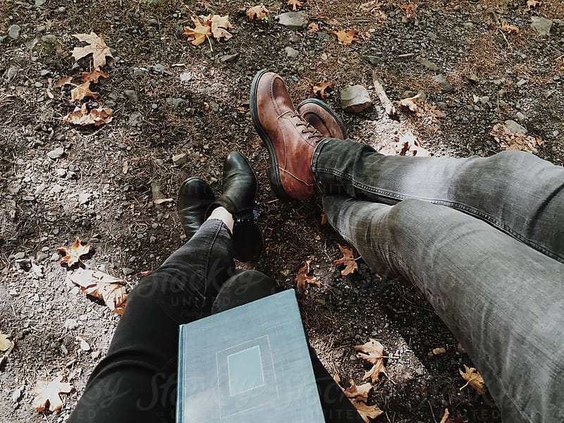 A man and a woman reading a book on a fall day by KATIE + JOE for Stocksy United