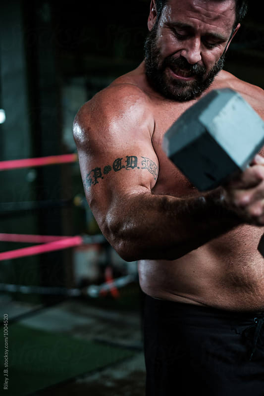 Muscular man lifting heavy dumbbell by Riley Joseph for Stocksy United