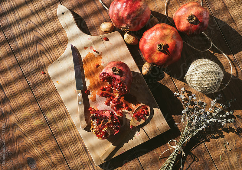 Overhead View of a Pomegranate on a Cutting Board by Mosuno for Stocksy United