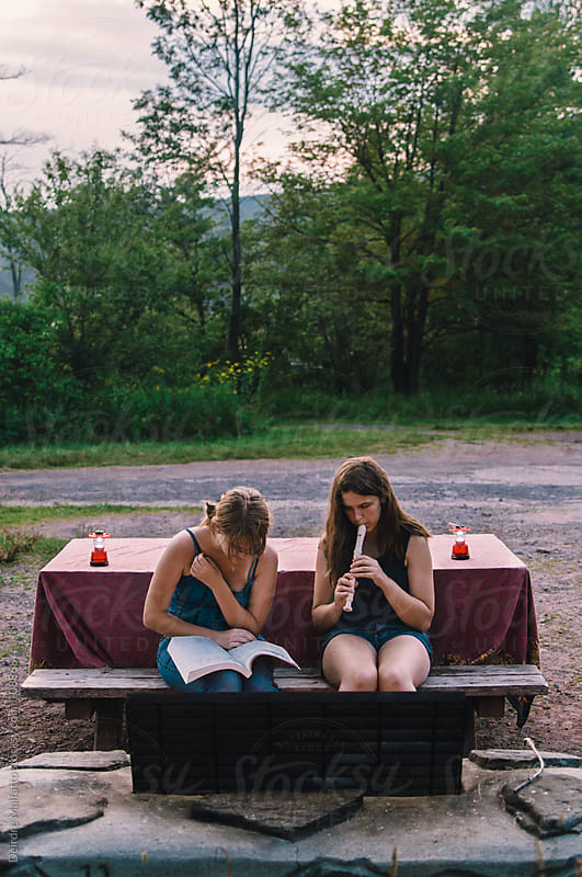 teenage sisters making music by a campfire by Deirdre Malfatto for Stocksy United
