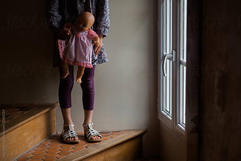 little girl holding doll in hands by Léa Jones for Stocksy United