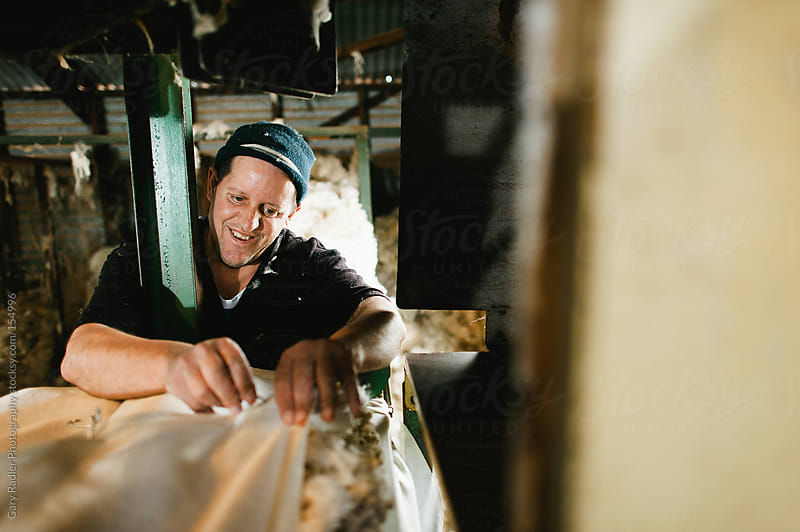 Farm Worker at Bale Machine in a Wool Shed by Gary Radler Photography for Stocksy United