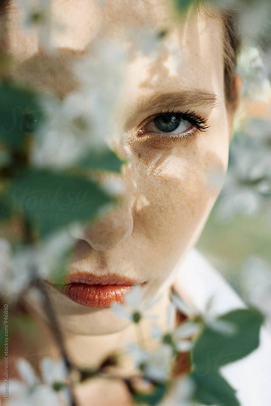 Blue eyes of young woman captured in tree by Hamza Kulenović for Stocksy United