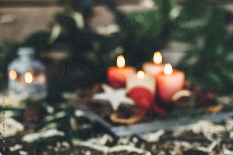 blurred advent wreath with four burning candles by Leander Nardin for Stocksy United
