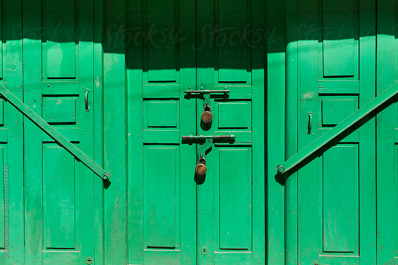 Locked green doors. by Shikhar Bhattarai for Stocksy United