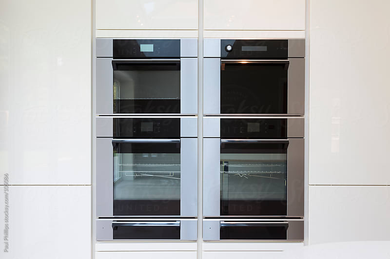 Modern integrated cooking unit set in white cabinets by Paul Phillips for Stocksy United