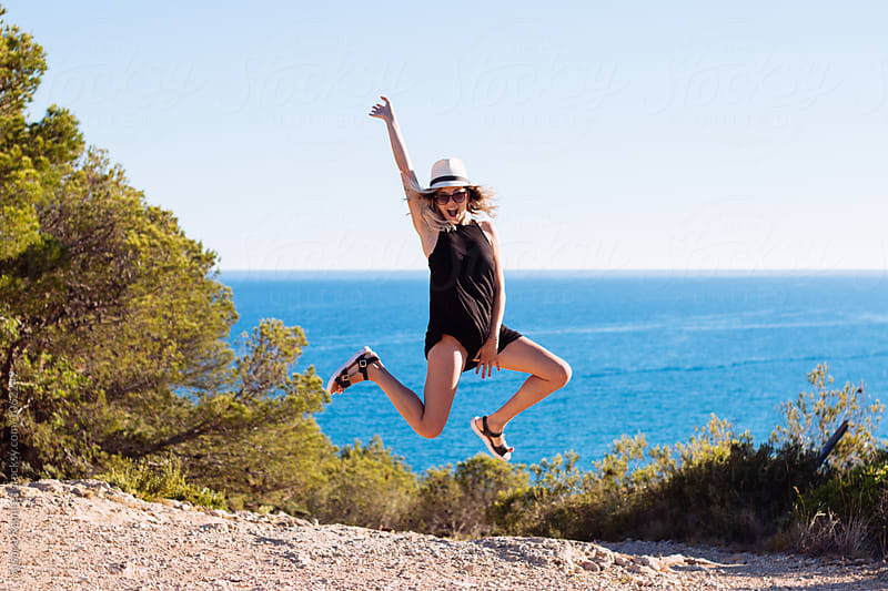 Portrait of young woman jumping on the field, with the sea background by Susana Ramírez for Stocksy United