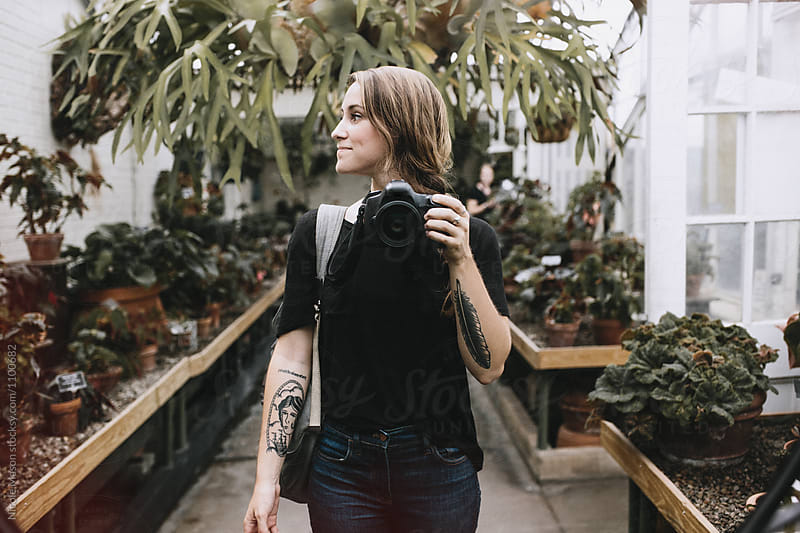 girl taking photo in mirror in greenhouse by Nicole Mason for Stocksy United