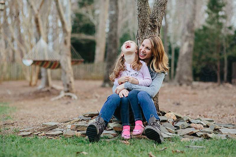 Mother and daughter sitting by the foot of a tree laughing and smiling by Jakob for Stocksy United