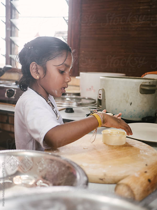Beautiful indian girl preparing dough in kitchen by Martin Matej for Stocksy United