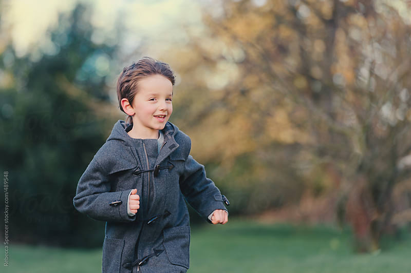 Boy in coat runs outdoors by Rebecca Spencer for Stocksy United