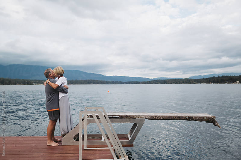 Older couple kissing together outside at lake by Rob and Julia Campbell for Stocksy United