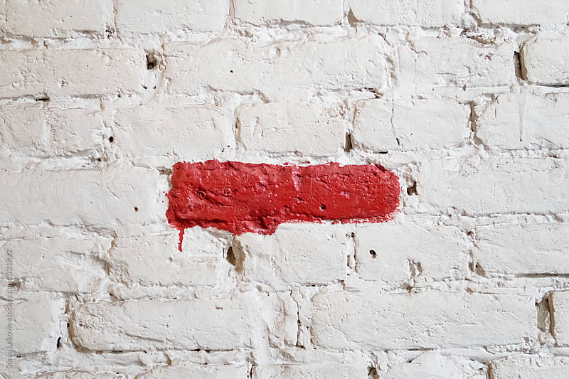 red painted line on a white brick wall by Sonja Lekovic for Stocksy United