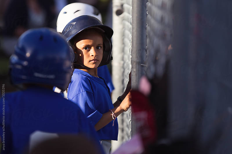 Young girl with baseball helmet and uniform with an intent look while waiting to bat by anya brewley schultheiss for Stocksy United