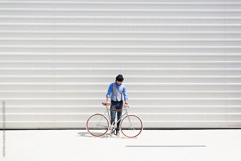 Young man looking at his bike by michela ravasio for Stocksy United