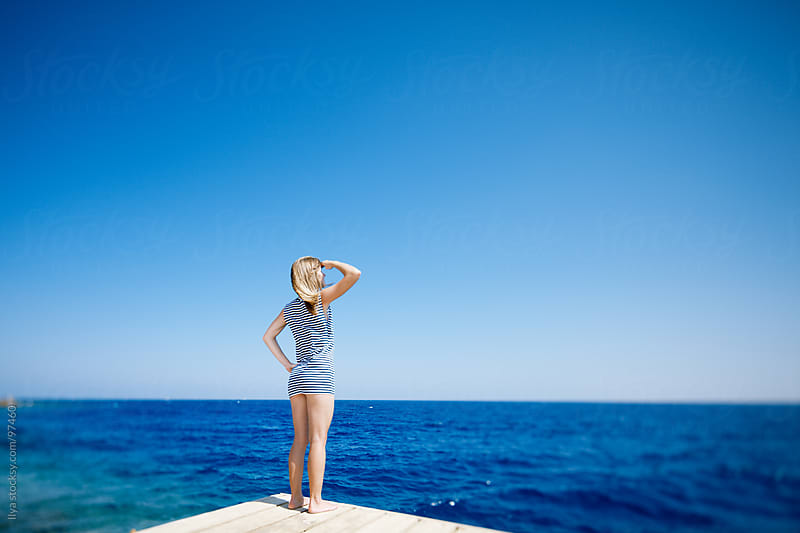 Young woman in sailors shirt standing on pier looking at sea by Ilya for Stocksy United