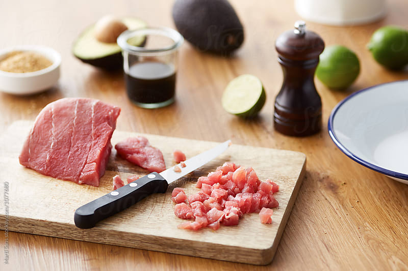 Pile of cut red tuna on board with knife by Martí Sans for Stocksy United