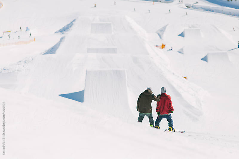 Two snowboarders on a ski slope. by Denni Van Huis for Stocksy United