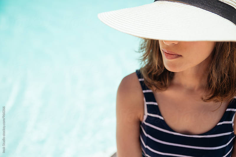 Close-up of woman in hat near swimming pool by Inuk Studio for Stocksy United