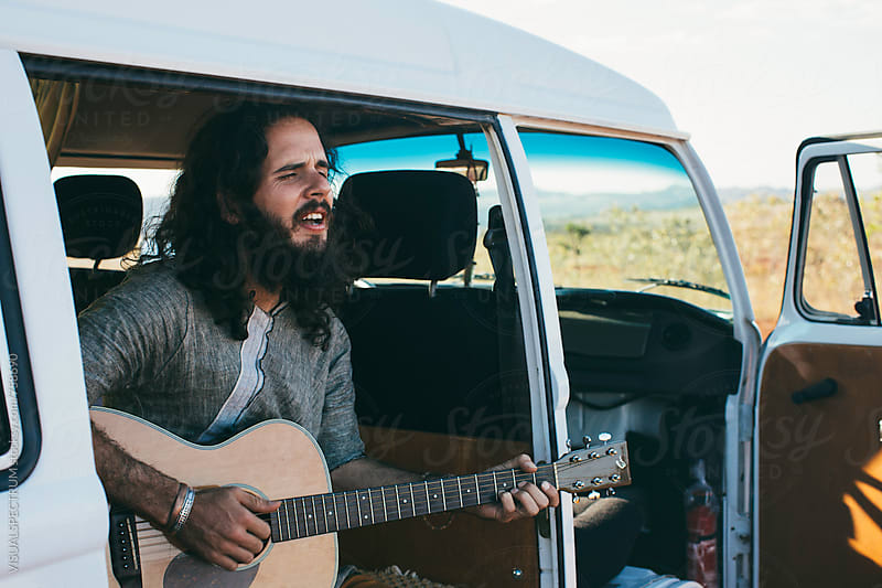 On The Road - Bearded Young Man Playing Guitar in White Camper Van by Julien L. Balmer for Stocksy United