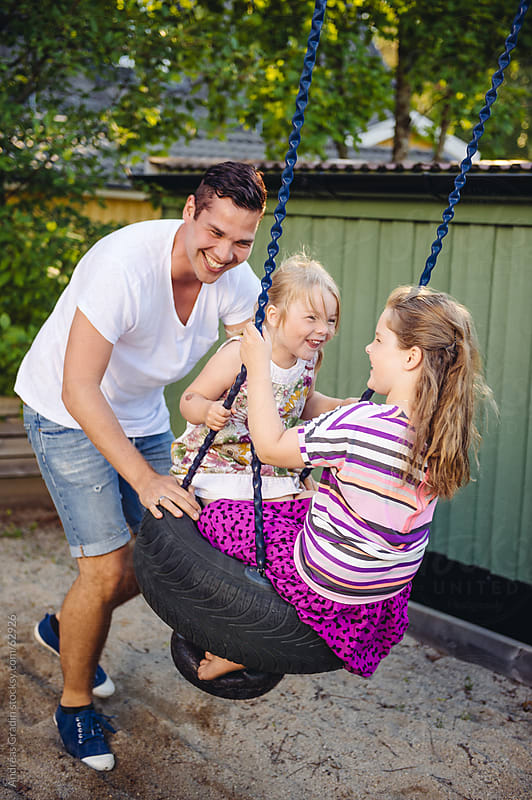 father and daughters playing by Andreas Gradin for Stocksy United