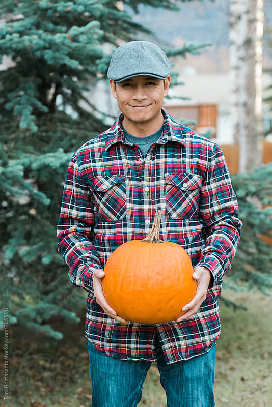 Smiling man in plaid shirt holding a pumpkin by Tara Romasanta for Stocksy United
