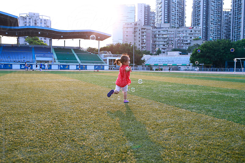 little girl running after bubble in the field by Bo Bo for Stocksy United