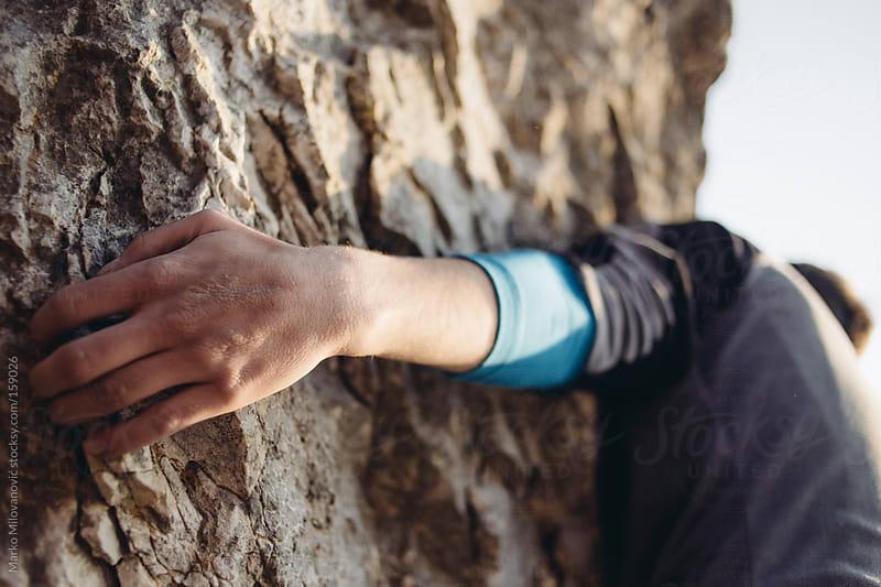 Man climbing natural rock, detail by Marko Milovanović for Stocksy United