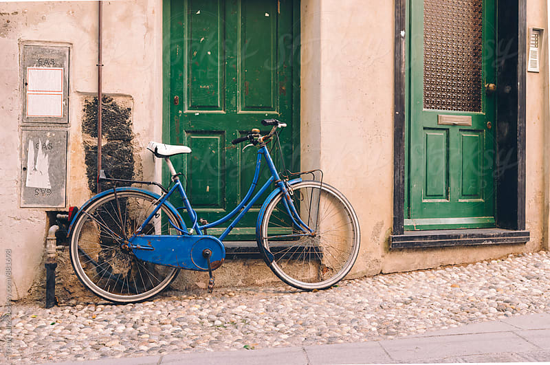 View on blue bicycle parked near green doors by Trent Lanz for Stocksy United