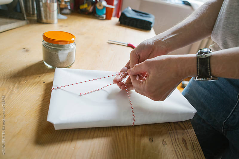 Close Up of Caucasian Woman Tying String on Parcel in Bright Dressmaking Atelier by Julien L. Balmer for Stocksy United