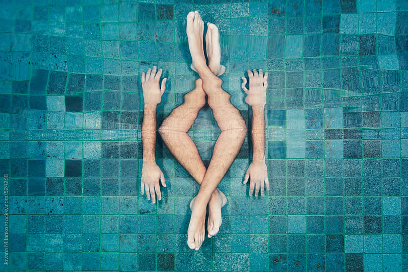 Man's feet and arm submerged underwater reflected of the surface of the swimming pool  by Jovana Milanko for Stocksy United
