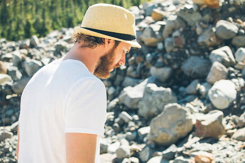 Blond Man With Beard Wearing Fedora And Looking Down In Riverbed by Luke Mattson for Stocksy United