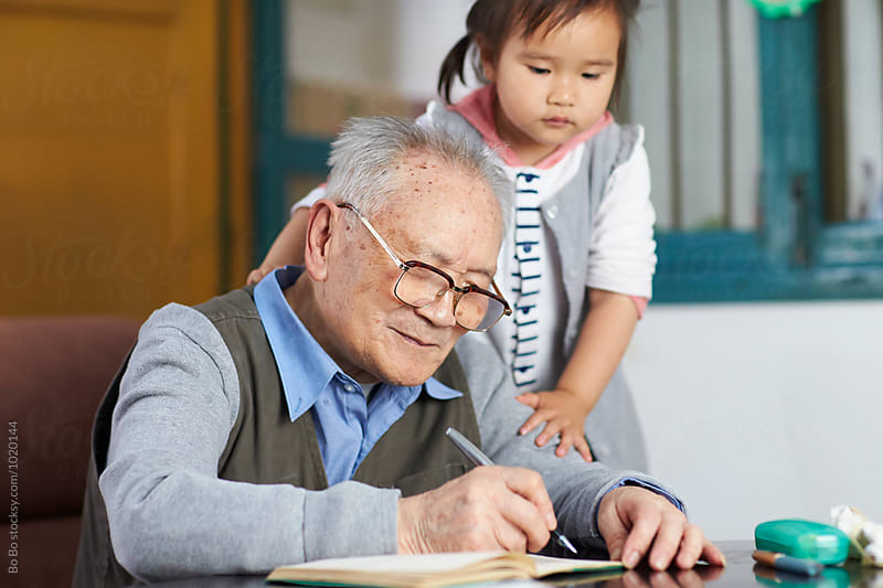 lovely little asian girl watch her great grandfather writing by Bo Bo for Stocksy United