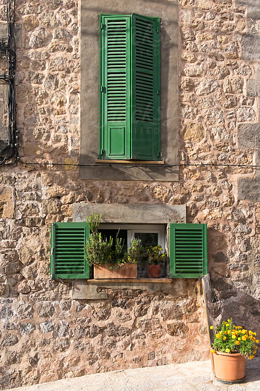 Green shutters and flower ornaments in a Mediterranean stone house by Marilar Irastorza for Stocksy United